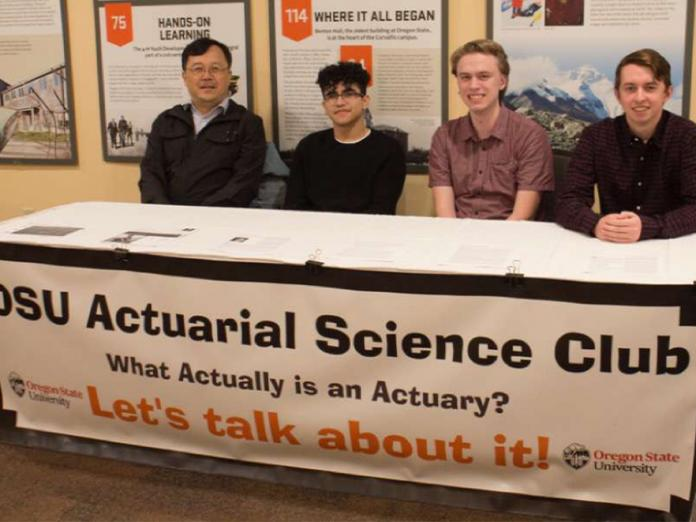 Actuarial science club members sitting at club booth.