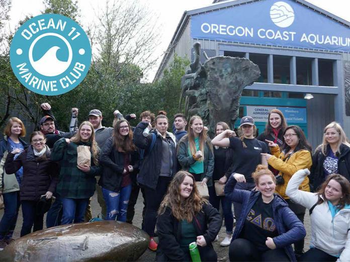 Ocean11 club members taking group picture in front of Oregon Coast Aquarium.