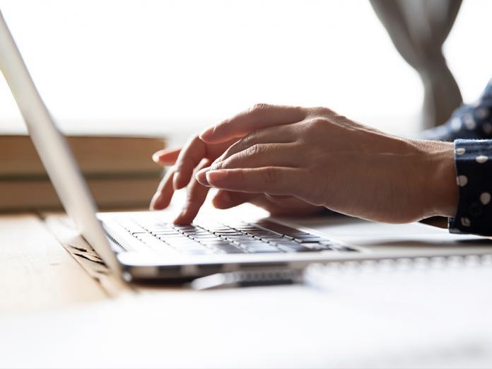 Student work on homework on laptop.