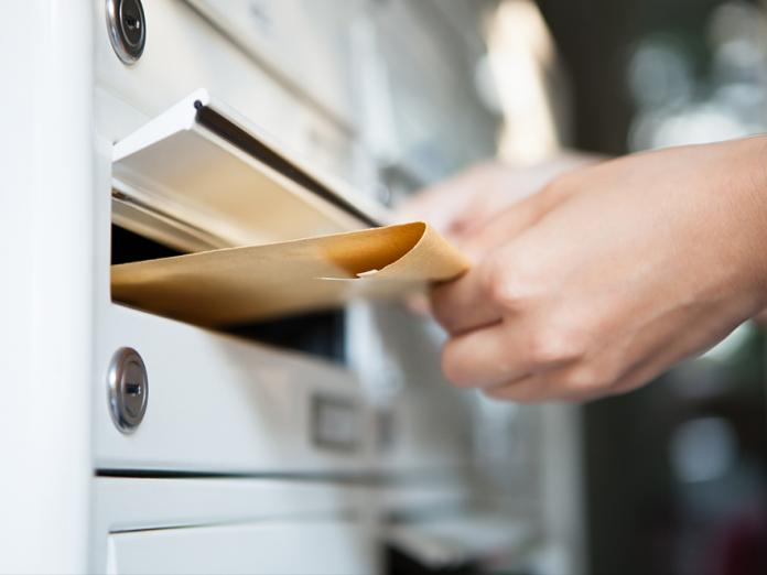 A closeup of a hand dropping an envelope into a mail slot in a facility.