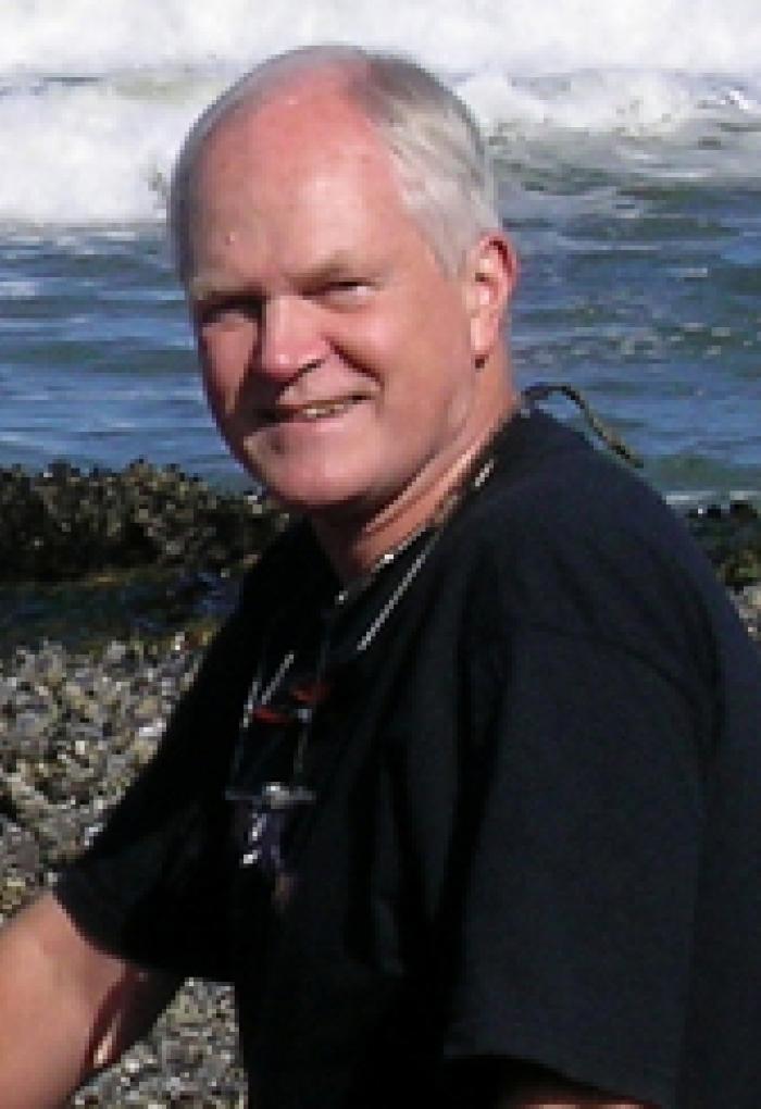 Bruce Menge sitting on beach