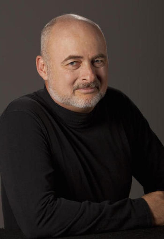 David Brin in front of grey backdrop