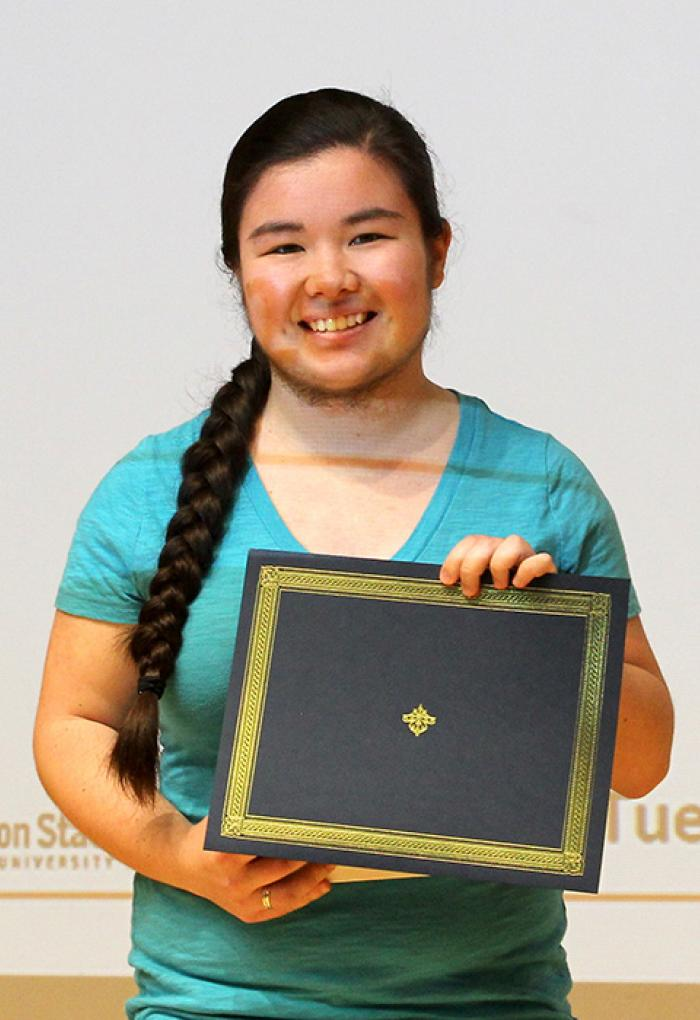 Celeste Wong holding up award on stage