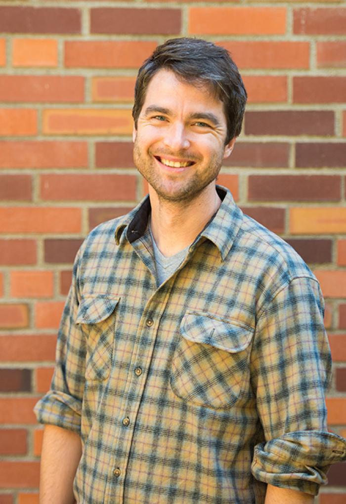 Ben Dalziel standing in front of bricks