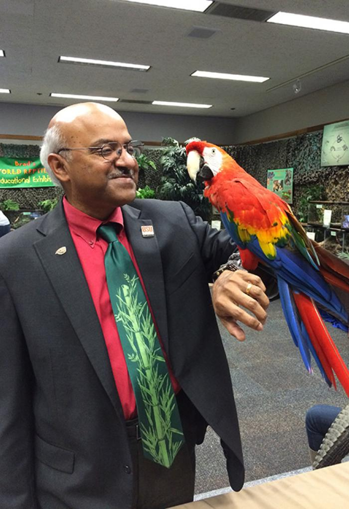 Sastry Pantula holding a scarlet macaw