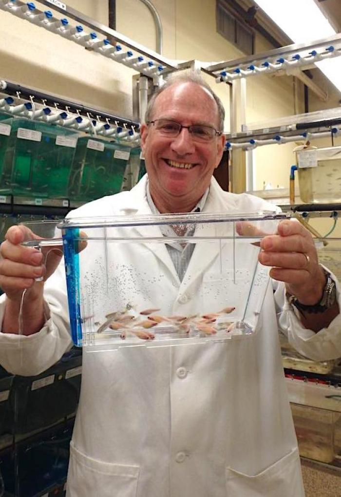 Michael Kent holding up tank of fish in lab