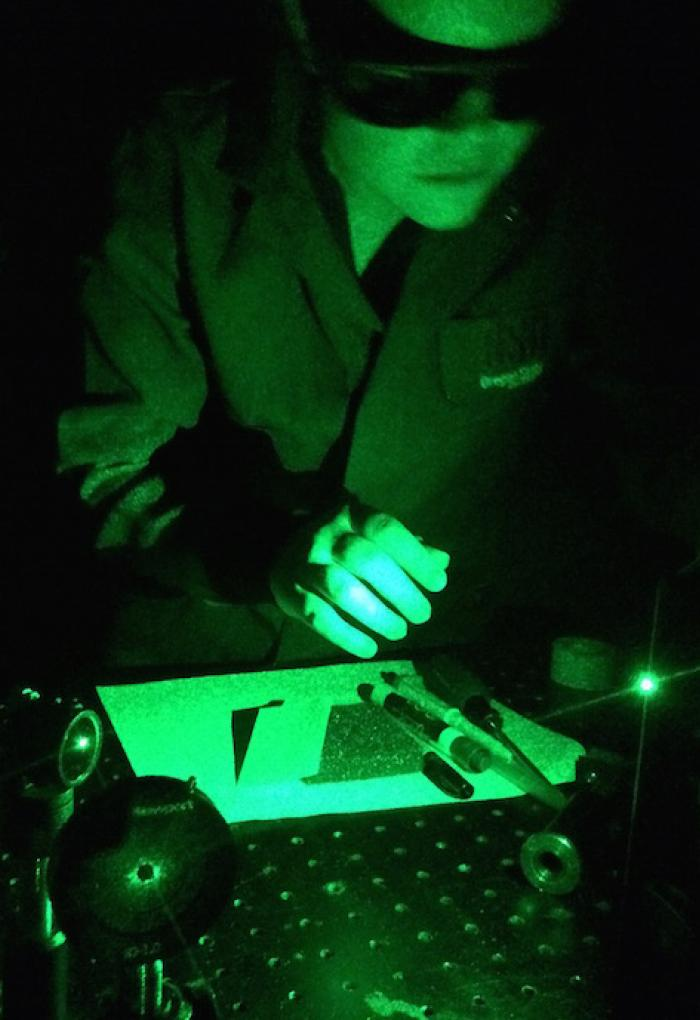 green light filter over Shan Lansing working with lab equipment