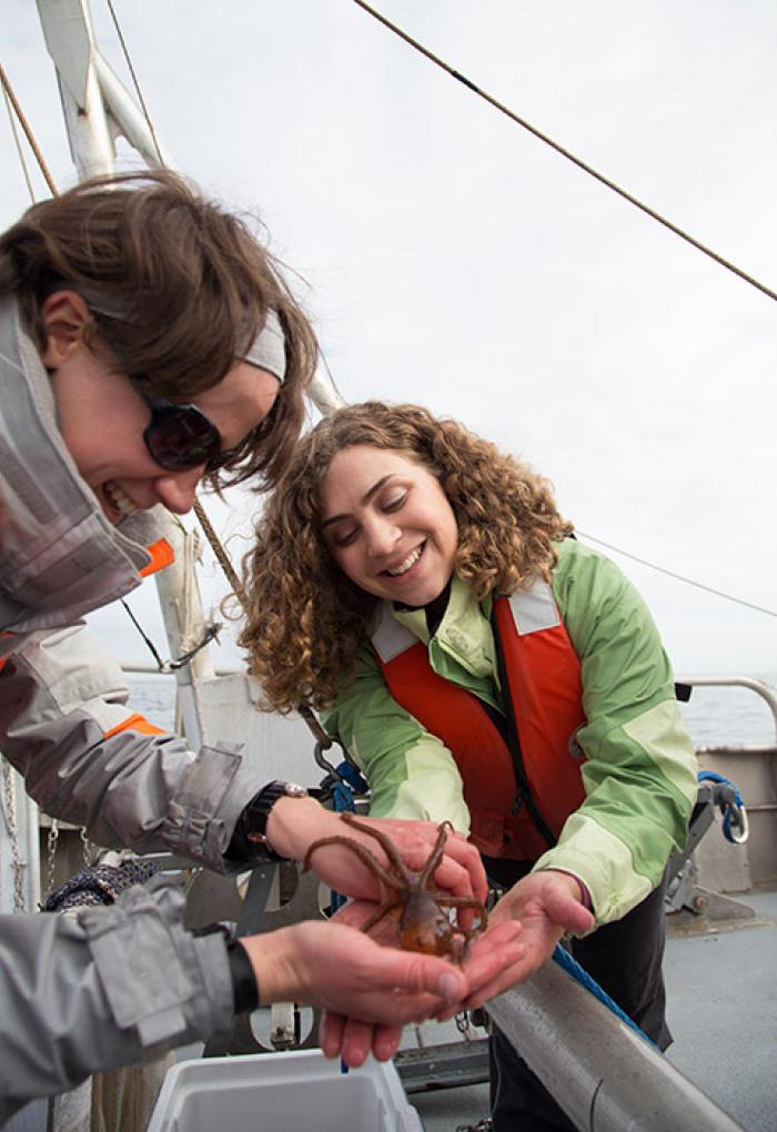Sarah Henkel and Lenaig Hemery holding small octopus on boat