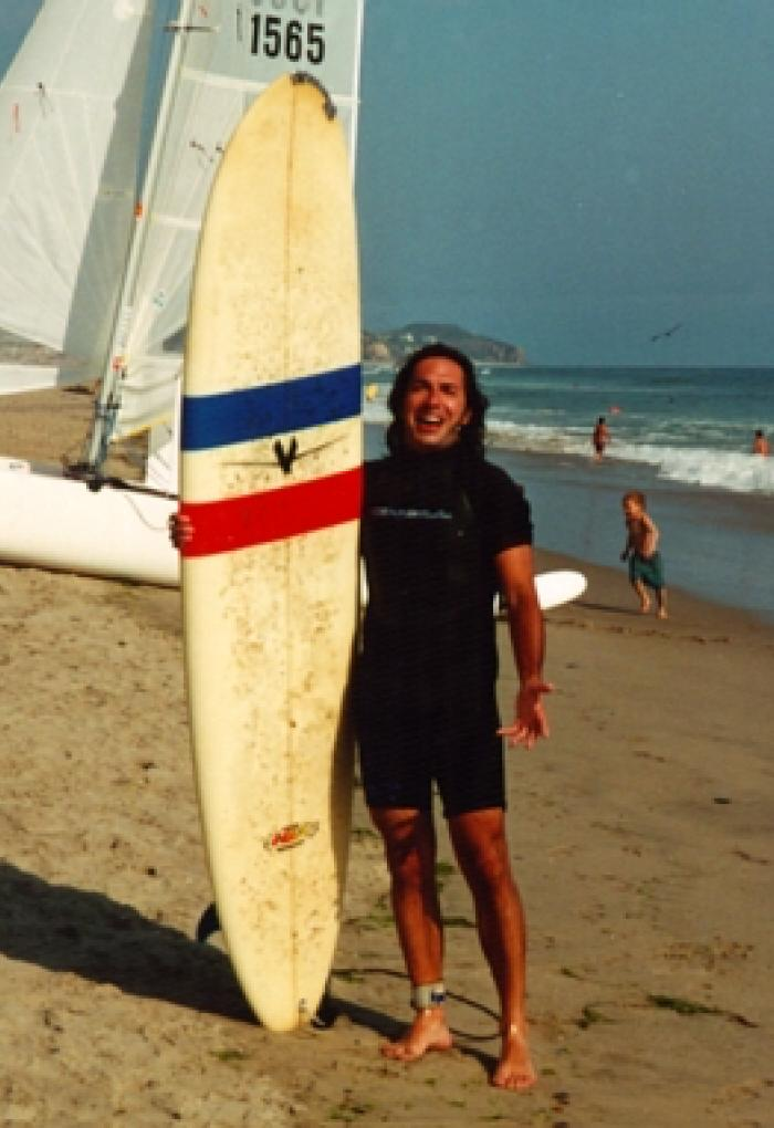 young Juan Restrepo standing on beach with surfboard