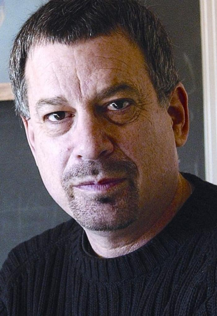 Andrew Blaustein in front of chalkboard