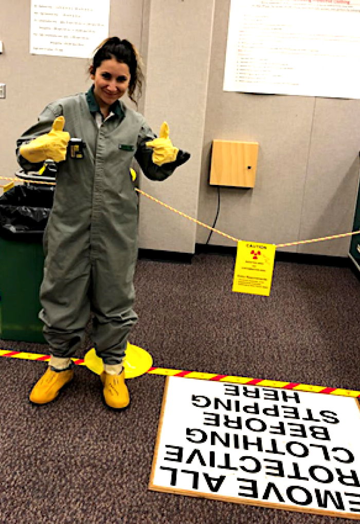 Ana Arteaga standing next to safety equipment in office