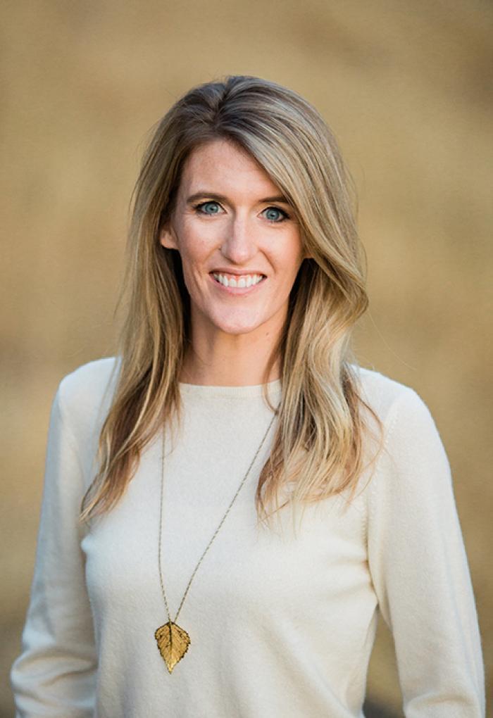 Megan Cook in front of beige backdrop