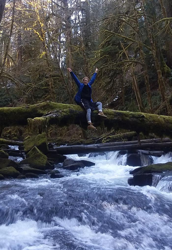 Girl with hands up sitting on a fallen log over a rushing river