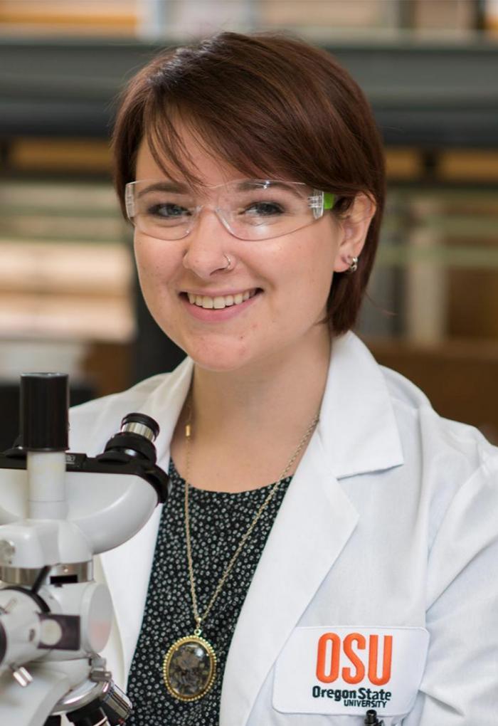 Microbiology Ph.D. student Grace Deitzler with microscope