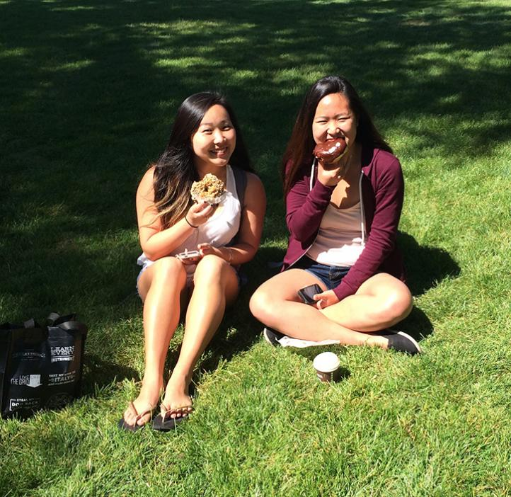 female students sitting in grass outside Valley Library