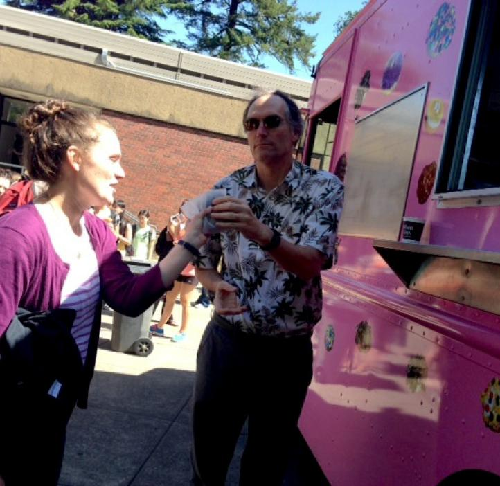 student grabbing donut from pink delivery truck
