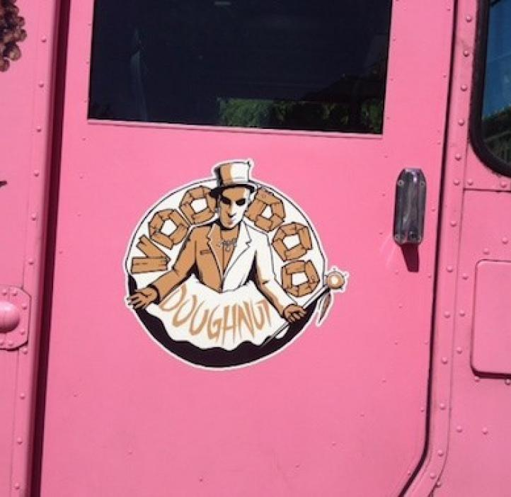pink delivery truck with Voodoo Doughnut logo