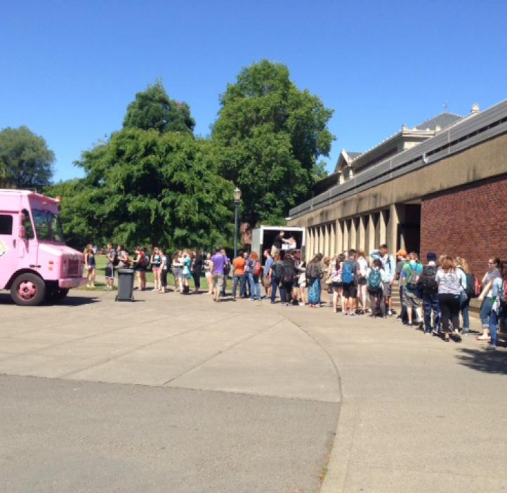 students lined up towards pink delivery truck