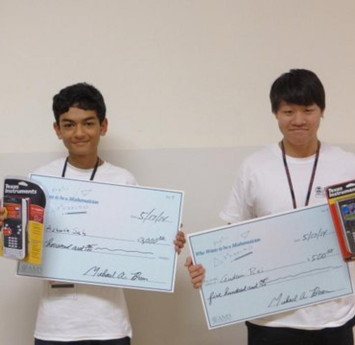 two male students holding awards in front of white backdrop