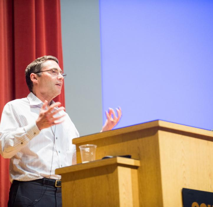 Carl Wieman speaking behind podium on stage