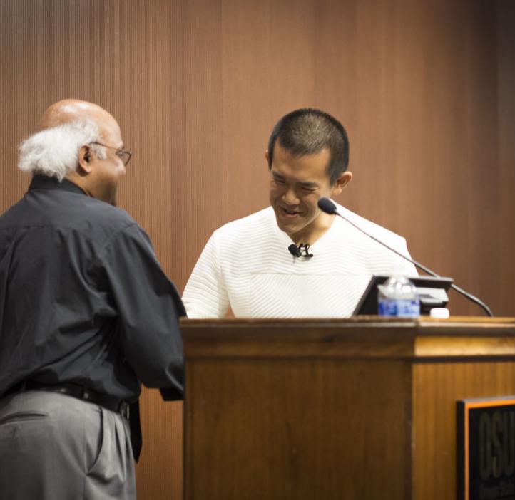 Ed Yong shaking hands with Sastry Pantula behind podium