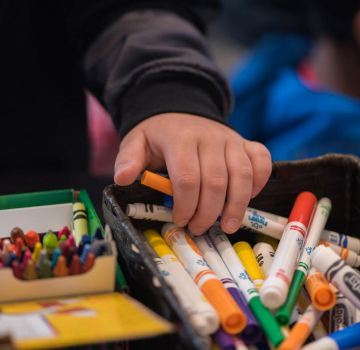 child grabbing crayons and markers from basket