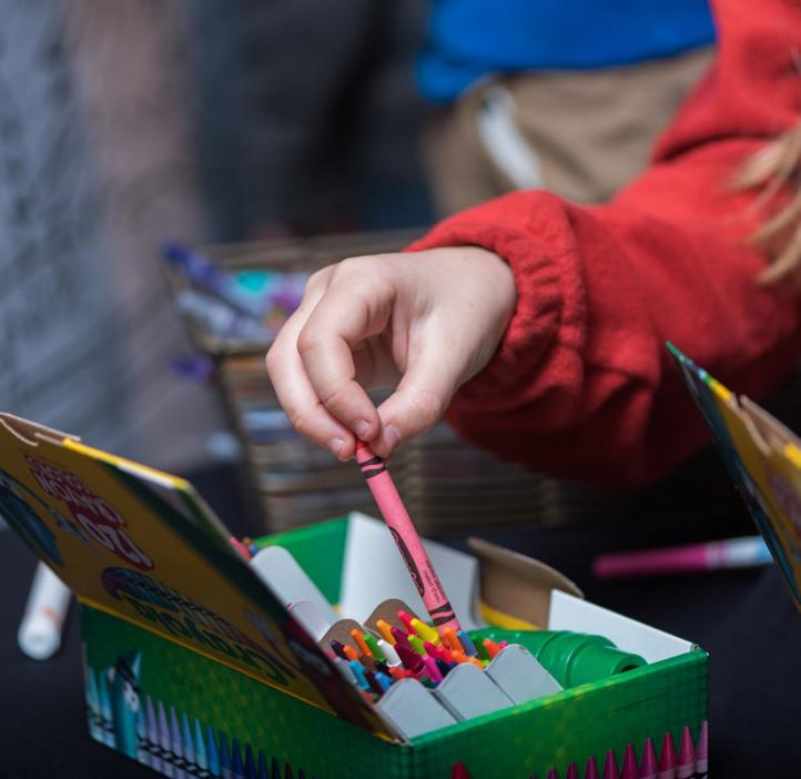 child grabbing crayon out of box