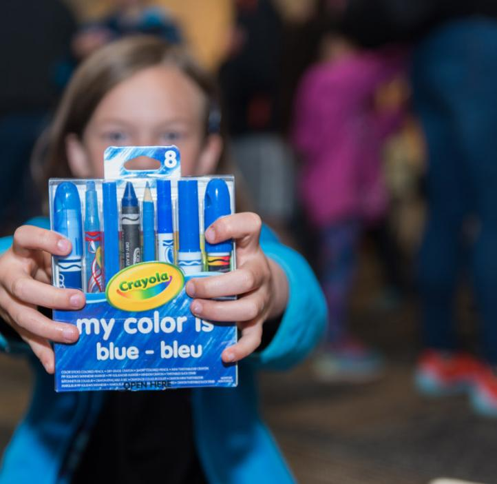 child holding blue Crayola package