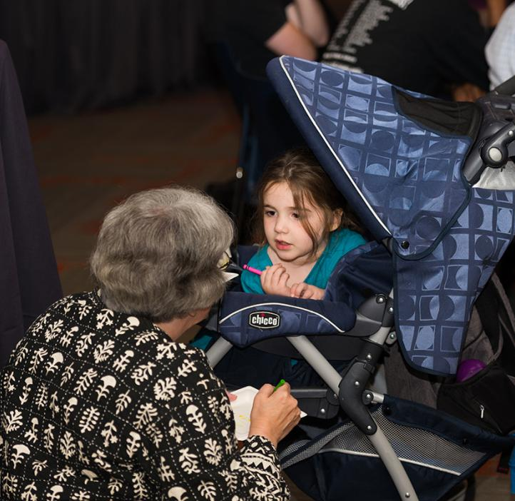 Young toddler in stroller chatting with elderly woman
