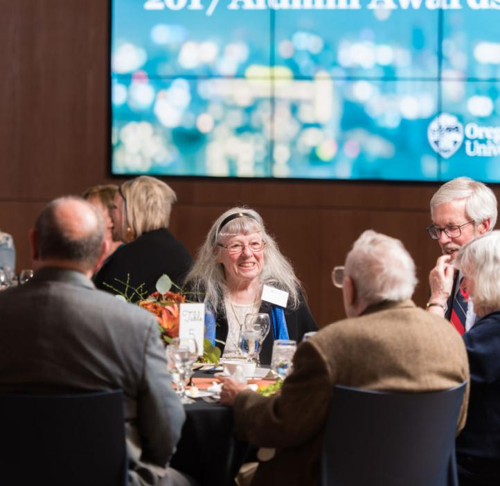 Christopher and Catherine Mathews chatting with colleagues at table