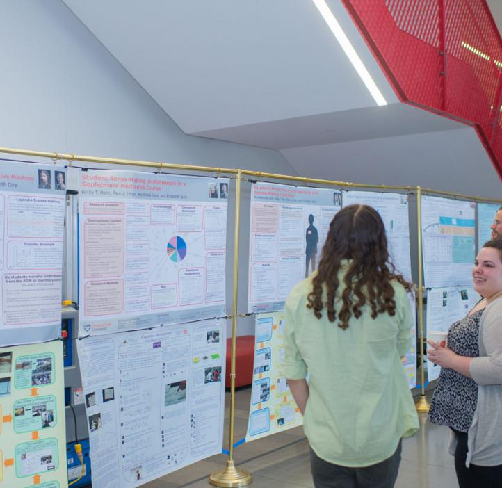 students looking through research posters