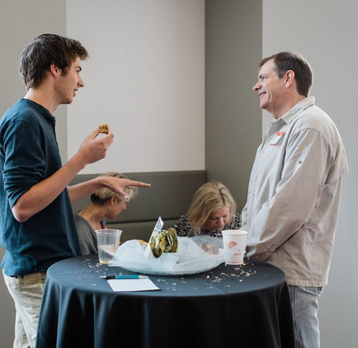 male student chatting with dad at table