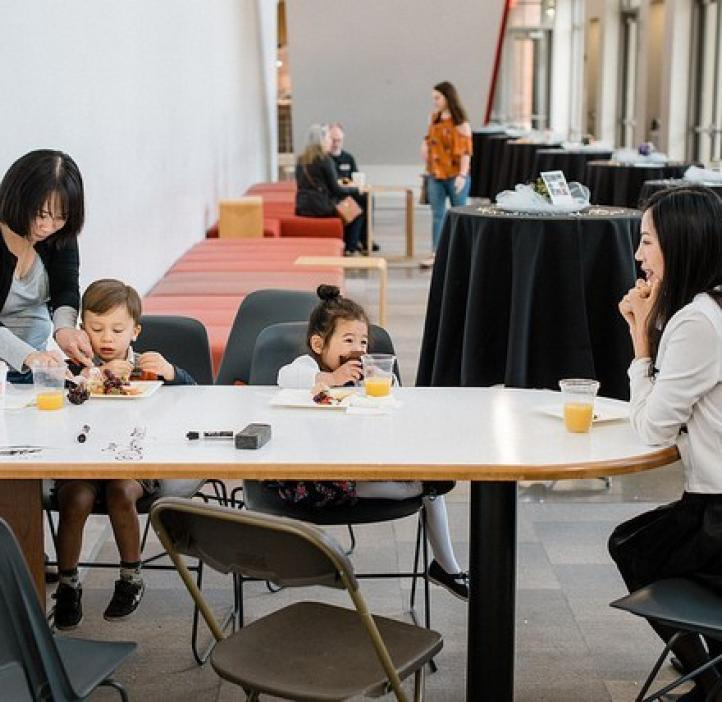 toddlers enjoying food with mothers at table