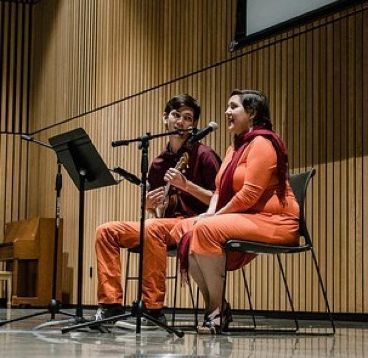 two students singing and playing ukulele on stage