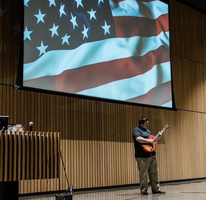 male student playing guitar with American flag behind him