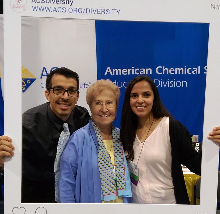two OSU SACNAS students and elderly woman holding up instagram interface poster