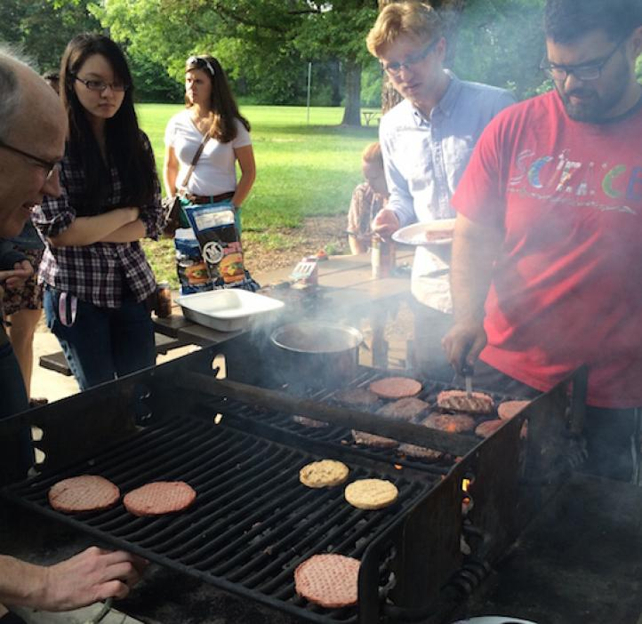 student and Karplus grilling burgers for students