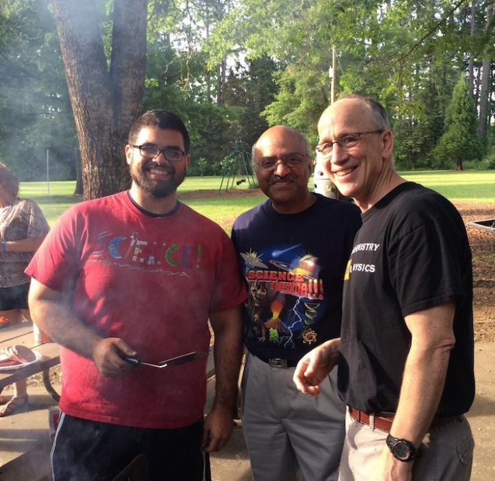 group photo of Karplus, Pantula, and student grilling burgers