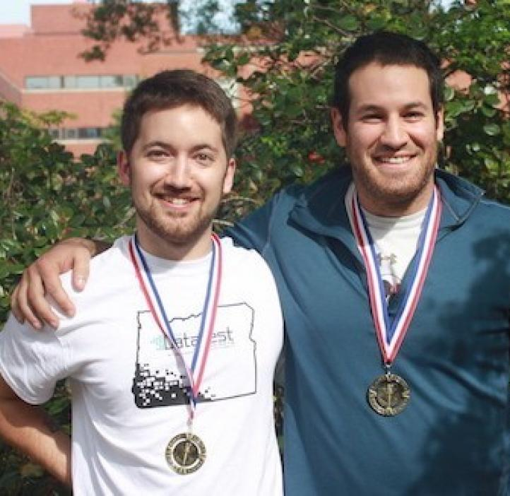 two male students wearing medals in front of shrubbery