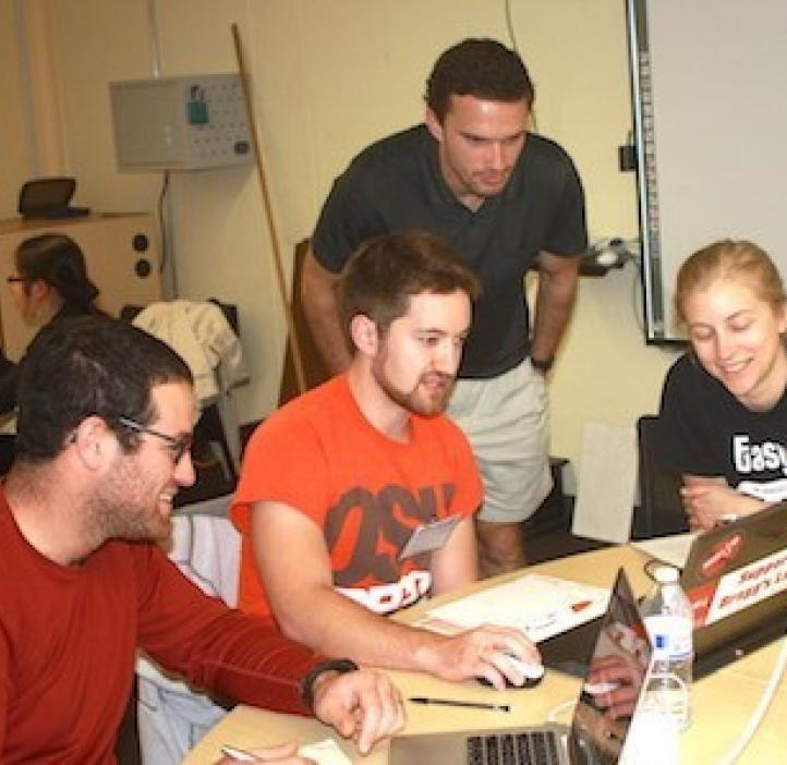 data science students working on laptops at table