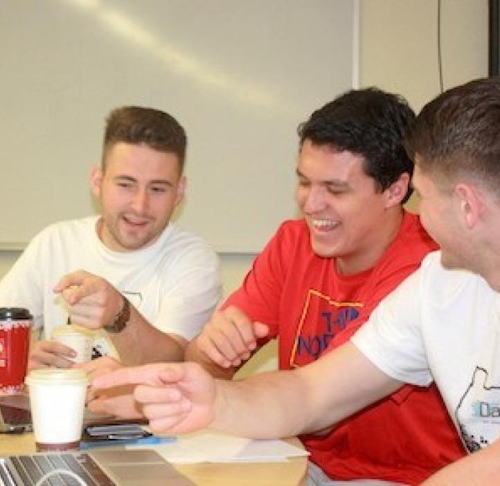 male students laughing while working on homework