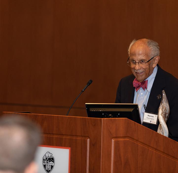 Warren Washington speaking behind podium