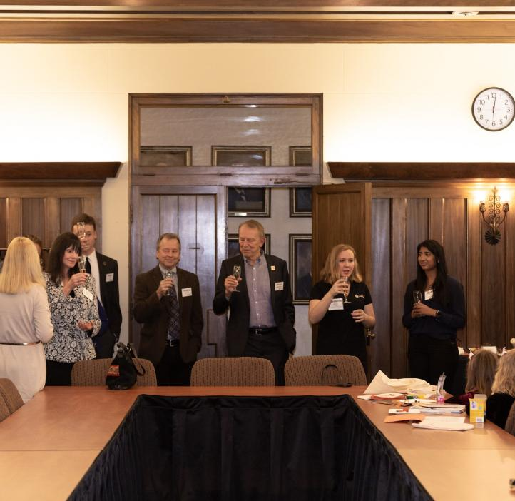 Faculty standing around table holding drinks