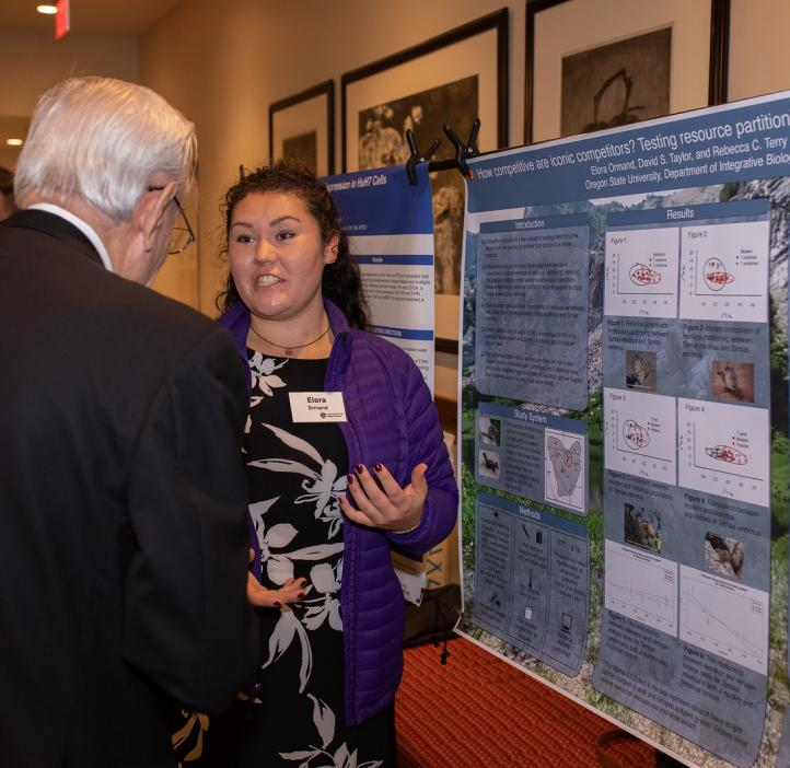 Elora Ormand speaking with colleague about her research poster