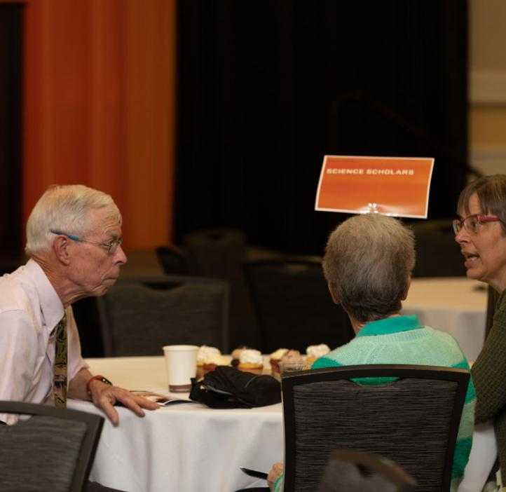 faculty chatting at table