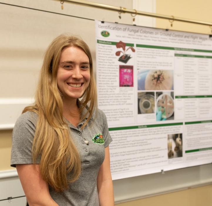 Jessica Scotten smiling next to her research poster