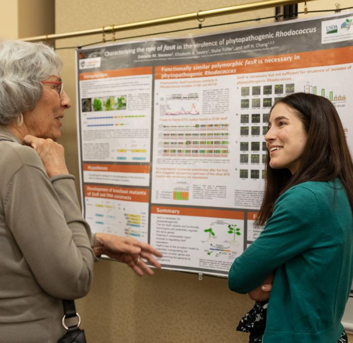 female student explaining her research poster with colleague