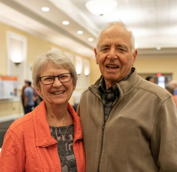 elderly couple hugging in lobby