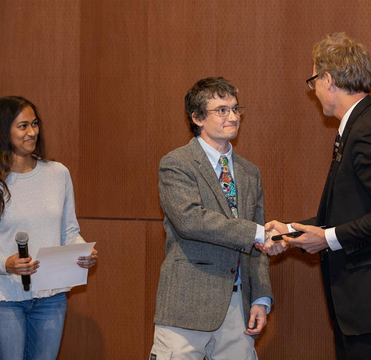 Nate Kirk shaking hands with Roy Haggerty and receiving award from student