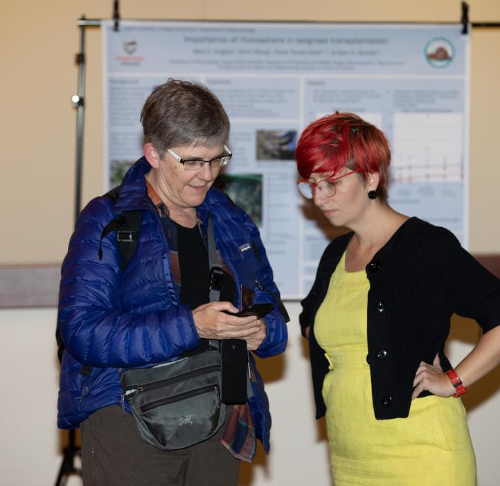Heidi M. Schellman and Gabs James chatting next to research posters